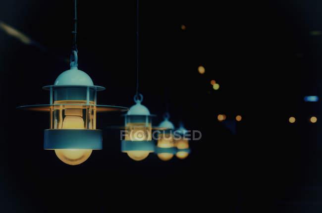 Linha de lâmpadas acesas na escuridão — Fotografia de Stock
