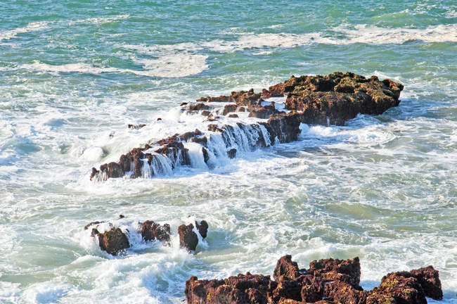 Waves breaking at rocky coastline — Stock Photo