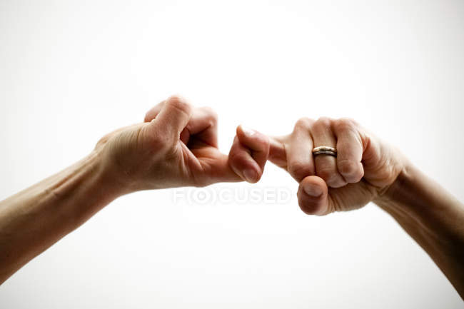Cropped view of people holding by little fingers — Stock Photo