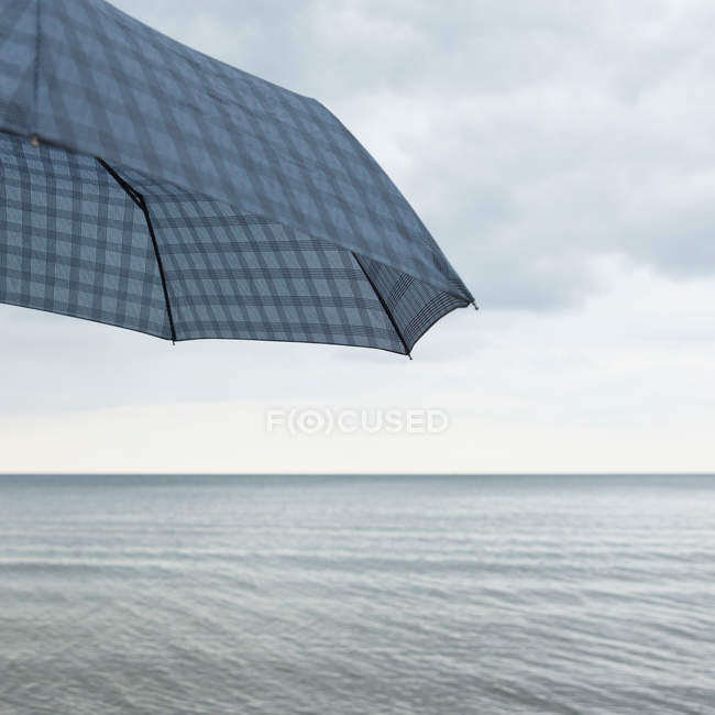 Parasol and seascape on background — Stock Photo