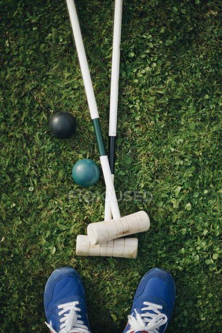 Крикет клуби, кулі та взуття на зелена трава газон — стокове фото