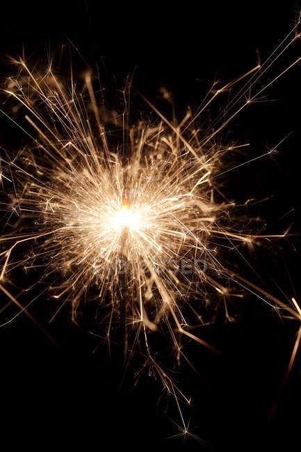 Closeup view of burning sparkler, dark background — Stock Photo