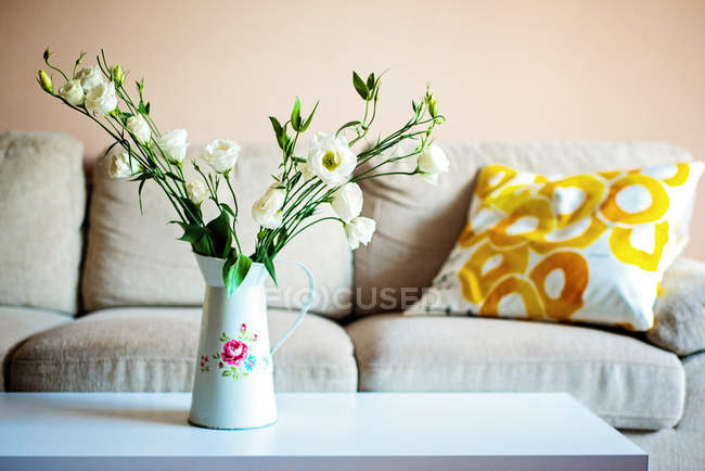 Home interior design, flowers in vase and sofa — Stock Photo