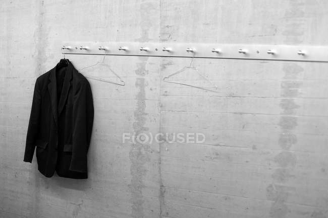 Grey wall with cloth hangers and black jacket — Stock Photo