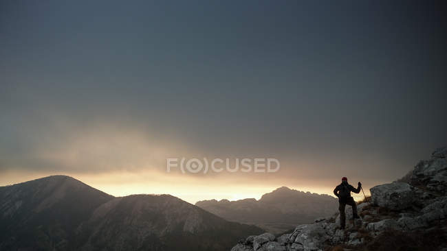 Traveler man hiking in mountains at sunset — Stock Photo