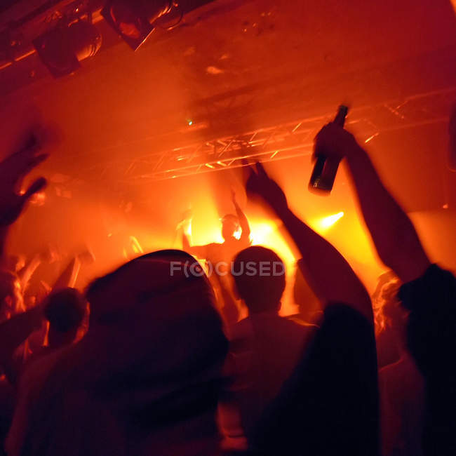 People crowd at concert, artist on the stage in red lights — Stock Photo