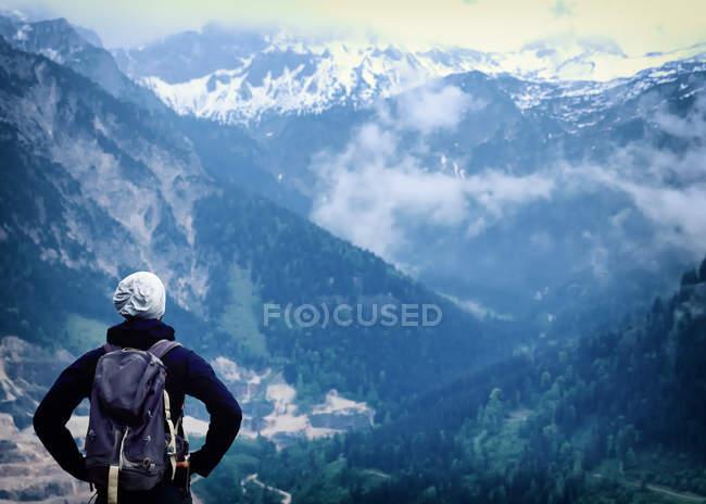 Vista posteriore di viaggiatore con lo zaino in montagne — Foto stock