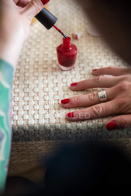 Female hands painting nails with red nail polish — Stock Photo