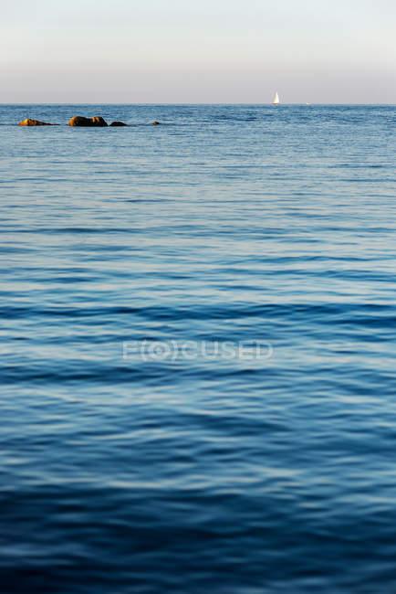 Море и небо, скалы в воду, парусная лодка на горизонте — стоковое фото