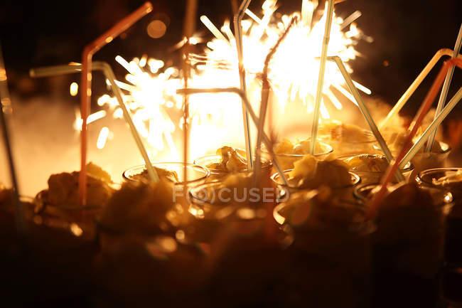 Cocktailgläser mit dem Trinken Strohhalme und Partei Funken auf Hintergrund — Stockfoto