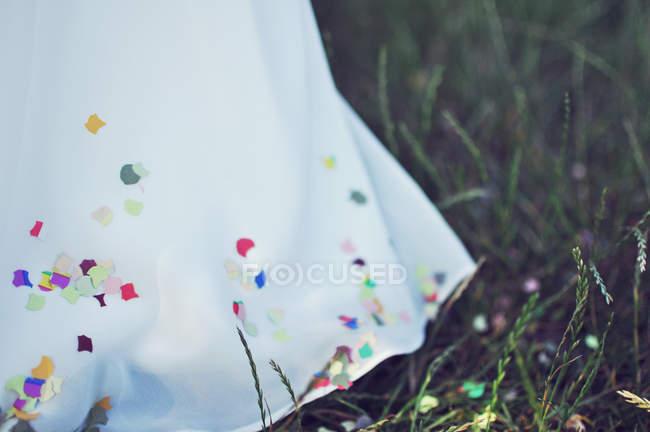 Wedding dress with confetti on it — Stock Photo