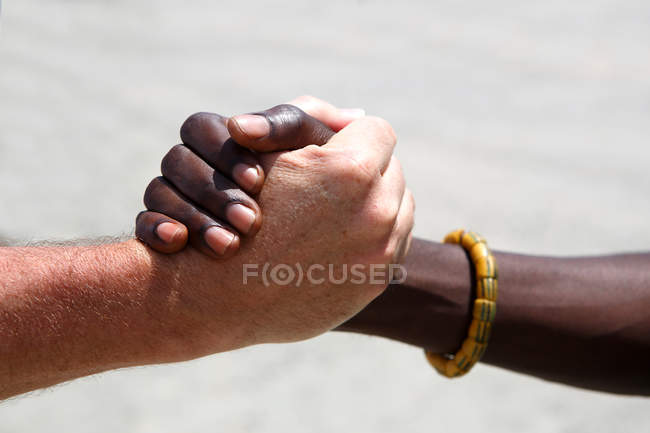 Cropped view of multiethnic people holding hands — Stock Photo