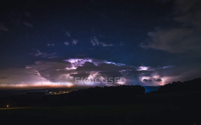 Purple clouds in night sky with thunderstorm — Stock Photo