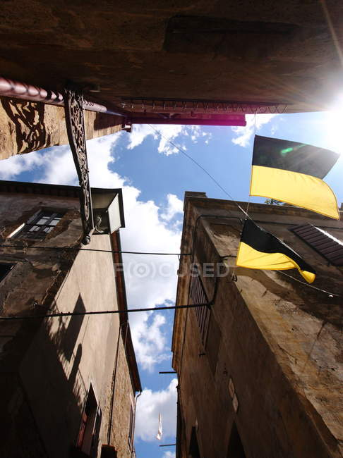 Bottom view of residential buildings of typical Italian architecture and flags, Pitigliano, Tuscany, Italy — Stock Photo