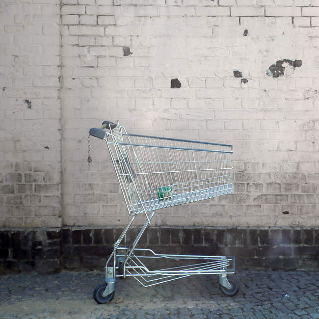Shopping trolley in front of brick wall — Stock Photo