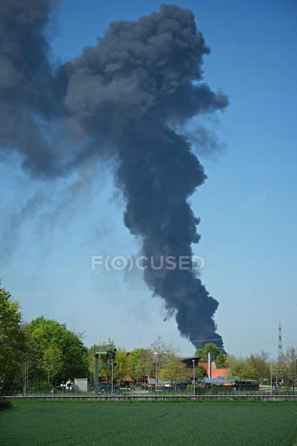 Lodernde Feuer mit dunkler Rauch in den Himmel, brennenden Haus — Stockfoto