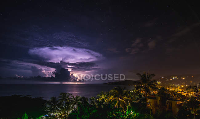 Purple lightning in night sky above sea and city — Stock Photo