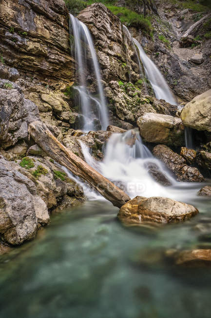 Forest waterfall and rocks overgrown with moss — Stock Photo