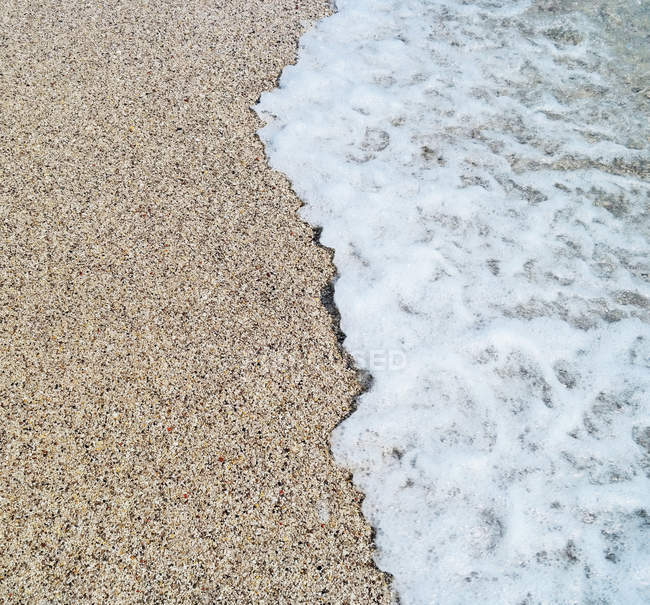 Sandy beach with sea water waves and foam — Stock Photo