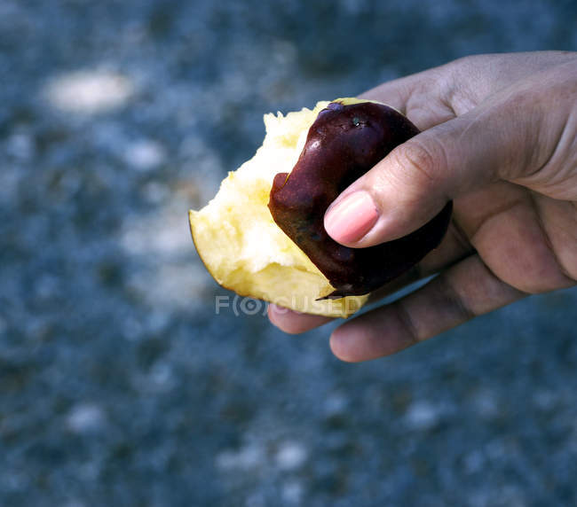 Human hand holding bitten apple — Stock Photo