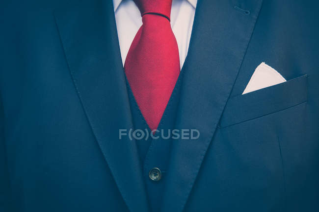Partial view of male business suit with white shirt and red tie — Stock Photo