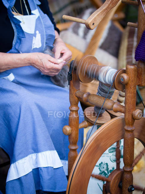 Senior woman working at vintage spinning-machine — Stock Photo