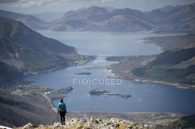 Pessoa de viajante em montanhas, olhando para o lago — Fotografia de Stock