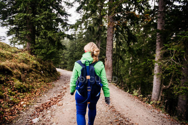 Traveler woman walking in mountains forest — Stock Photo