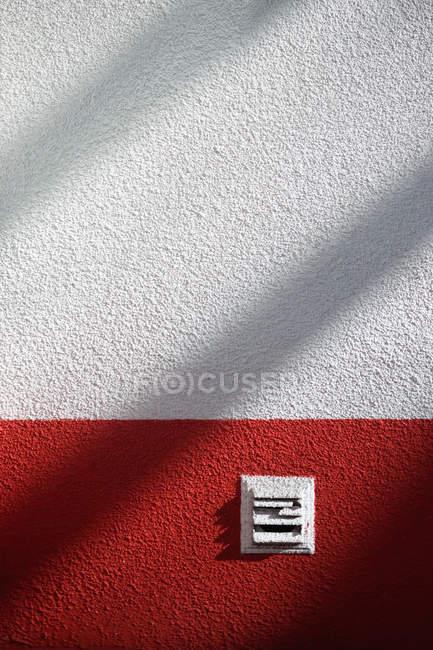 Pura parede branca com uma listra vermelha e sombras — Fotografia de Stock