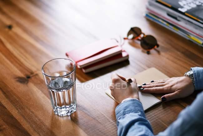 Vue recadrée de femme prenant des notes une table en bois avec verre d'eau et les ordinateurs portables — Photo de stock