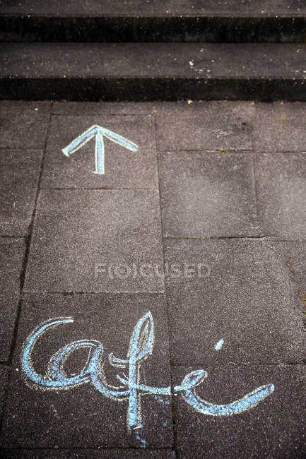 Cafe word and arrow written on tiled pavement with white and blue chalk — Stock Photo