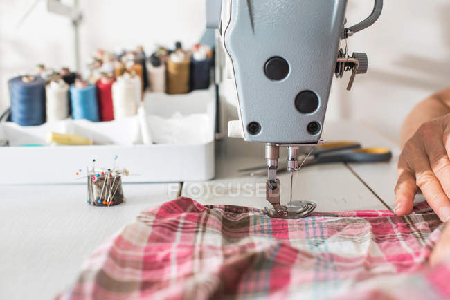 Sewing threads on tailor table with sewing machine — Stock Photo