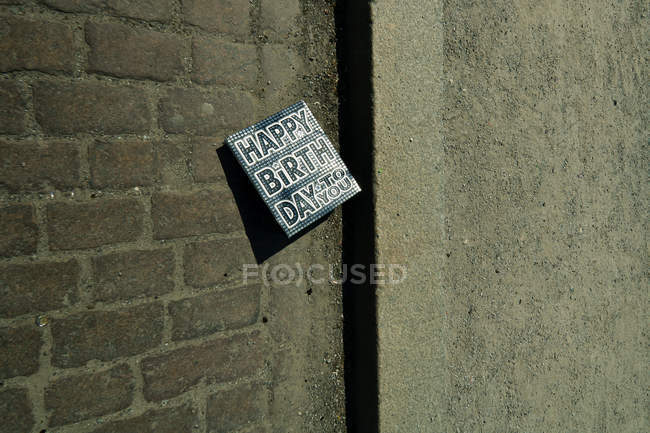 Congratulation card with Happy birth day to you words on dark brick wall — Stock Photo