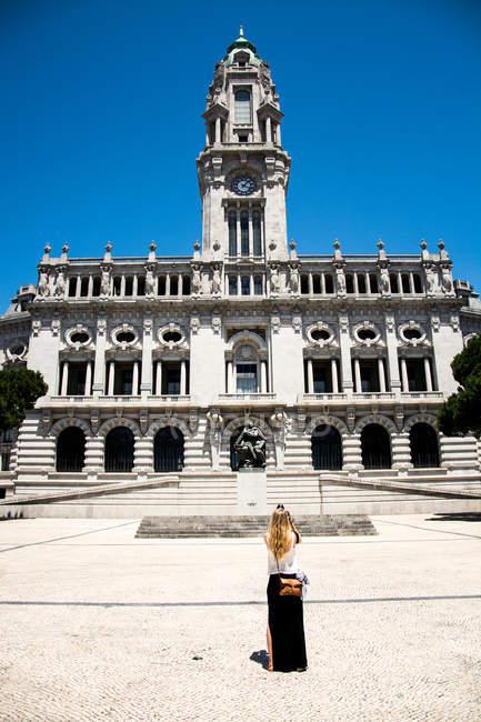Vista posteriore di donna turistica che sta contro il Municipio storico in porto — Foto stock