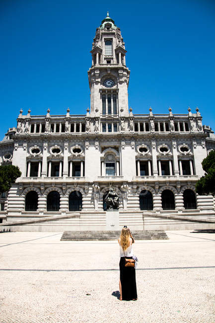 Back view of tourist woman standing against historic city hall in porto — Stock Photo