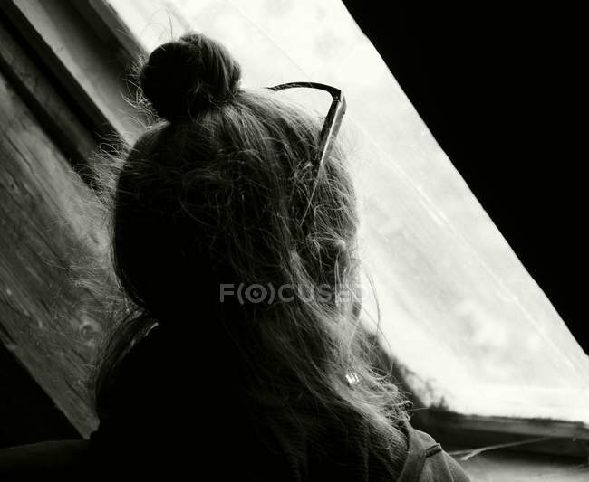 Rear view of woman with glasses looking at window, monochrome — Stock Photo