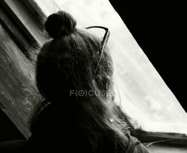 Vista posteriore della donna con i vetri, guardando la finestra, monocromatico — Foto stock