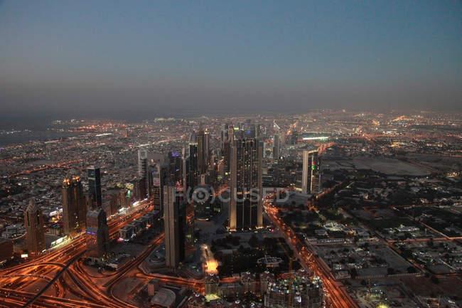 Vista aérea del paisaje urbano de la metrópoli de Dubai iluminada en la oscuridad, Emiratos Árabes Unidos - foto de stock