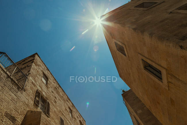 Wide angle, exterior shot of old town buildings facades and sun in blue sky — Stock Photo