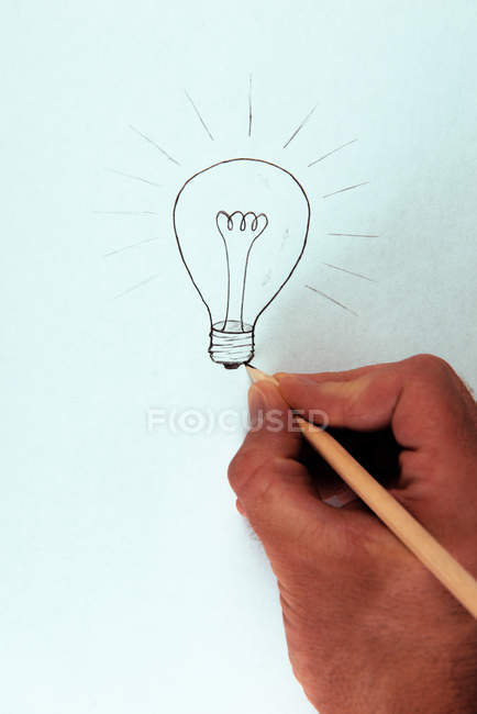 Creative person drawing on paper light bulb with pencil — Stock Photo