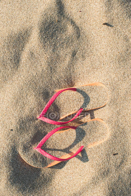 Pink flip flops on the beach in sand — Stock Photo