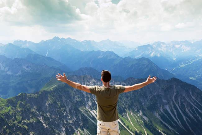 Резервного зору щасливий чоловік, що стоїть на вершині гори — стокове фото