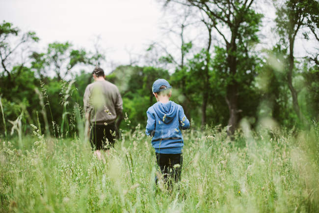 Rear view of father with son walking in green grass — Stock Photo