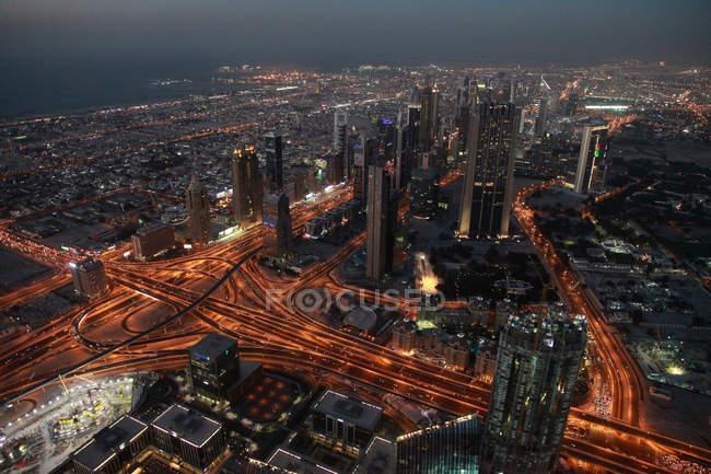 Paisaje aéreo de urbe de Dubai con arquitectura moderna iluminada al atardecer, Emiratos Árabes Unidos - foto de stock