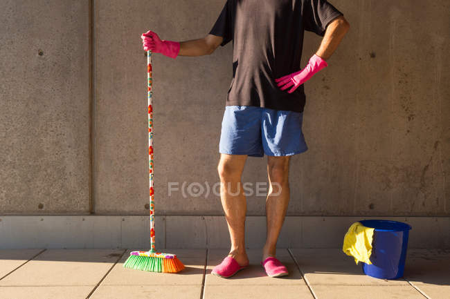 Man in colorful slippers wearing pink rubber gloves, holding broom, blue plastic bucket and rag on the floor — Stock Photo