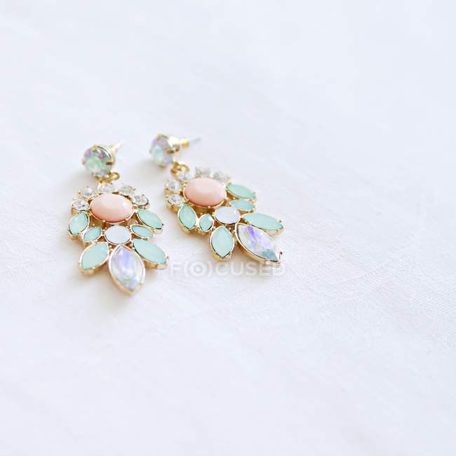 Closeup view of two earrings with gems on white surface — Stock Photo
