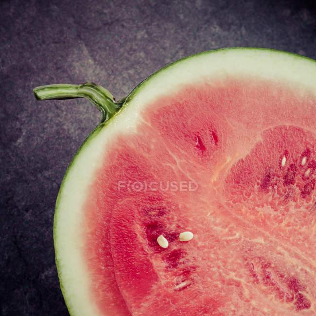 Watermelon half on black surface — Stock Photo