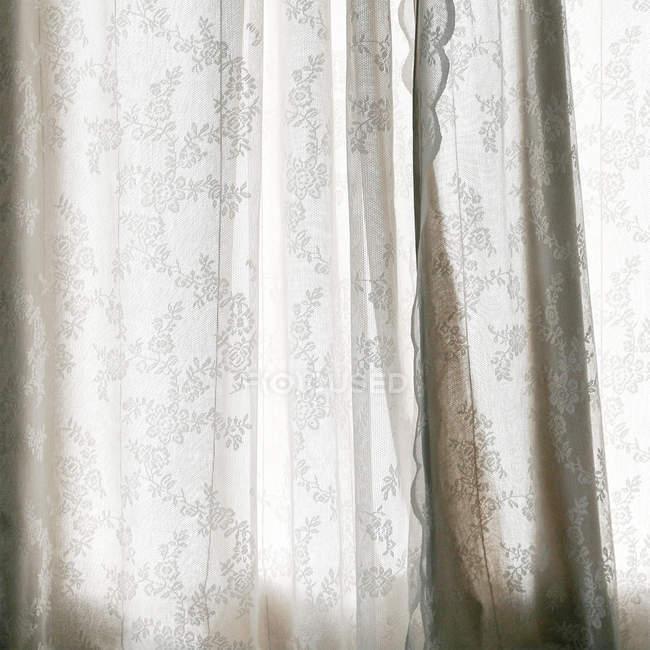 Vista diurna de cortinas blancas con dibujos en la ventana - foto de stock
