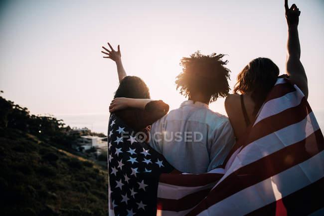 Заднього виду з трьох американських підлітків загорнуті в США прапор — стокове фото