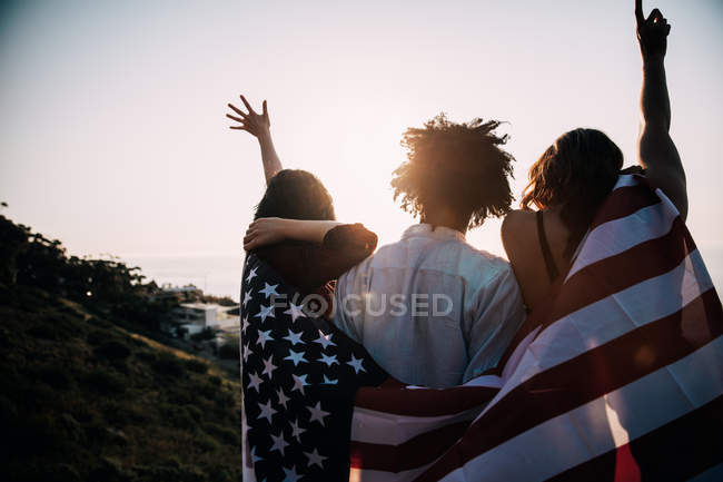 Rear view of three american teenagers wrapped in usa flag — Stock Photo